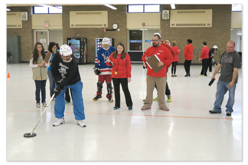 Canon volunteers assist players at the Special Olympics Hockey Tournament.