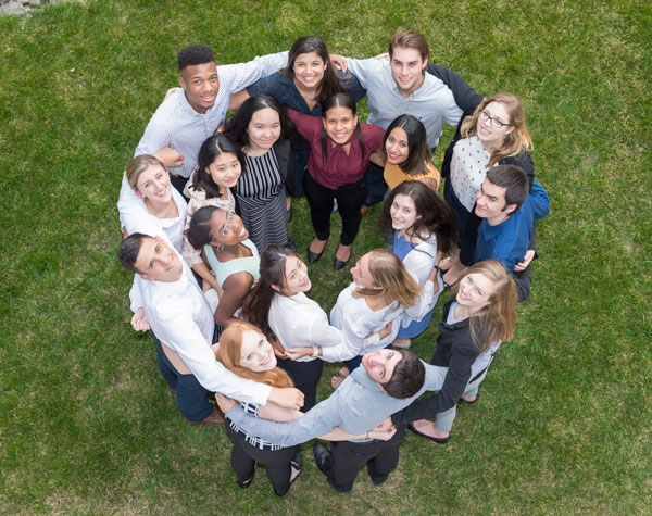 Image of student interns standing in a circle and smiling at the camera
