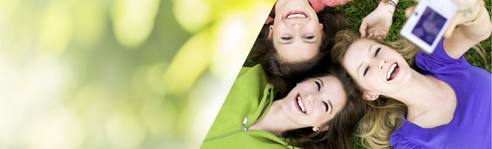 Three girls lying in grass with camera taking selfies