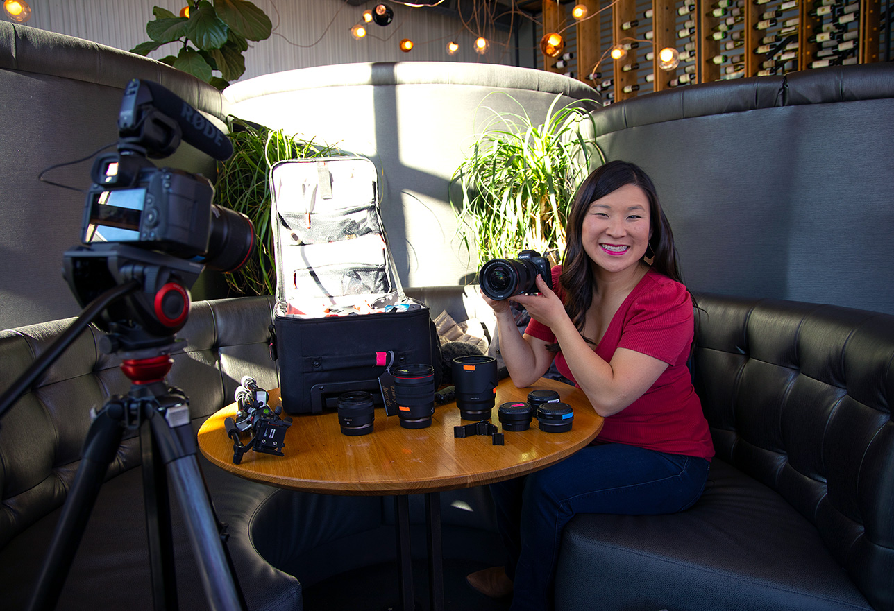 Jules smiling and holding the Canon EOS R in a booth with gear