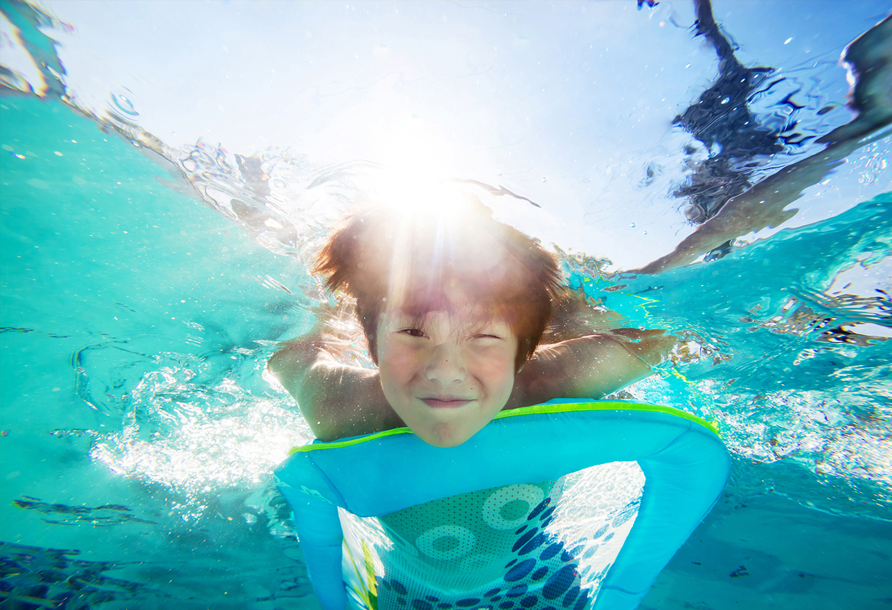 Photo of boy smiling under water in a pool