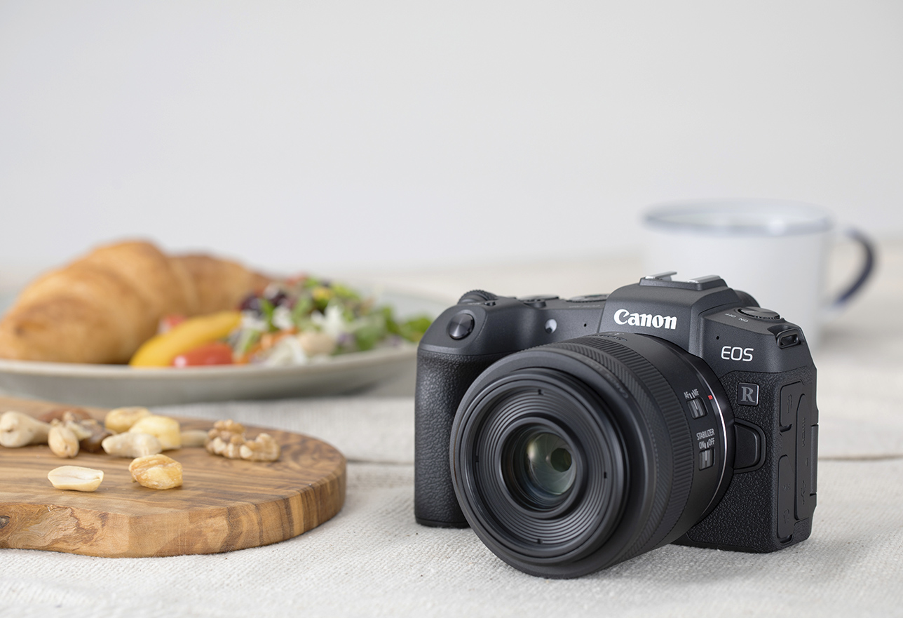 Canon EOS RP camera beside a cutting board of assorted nuts, a plate with a croissant and side salad and a white and blue mug