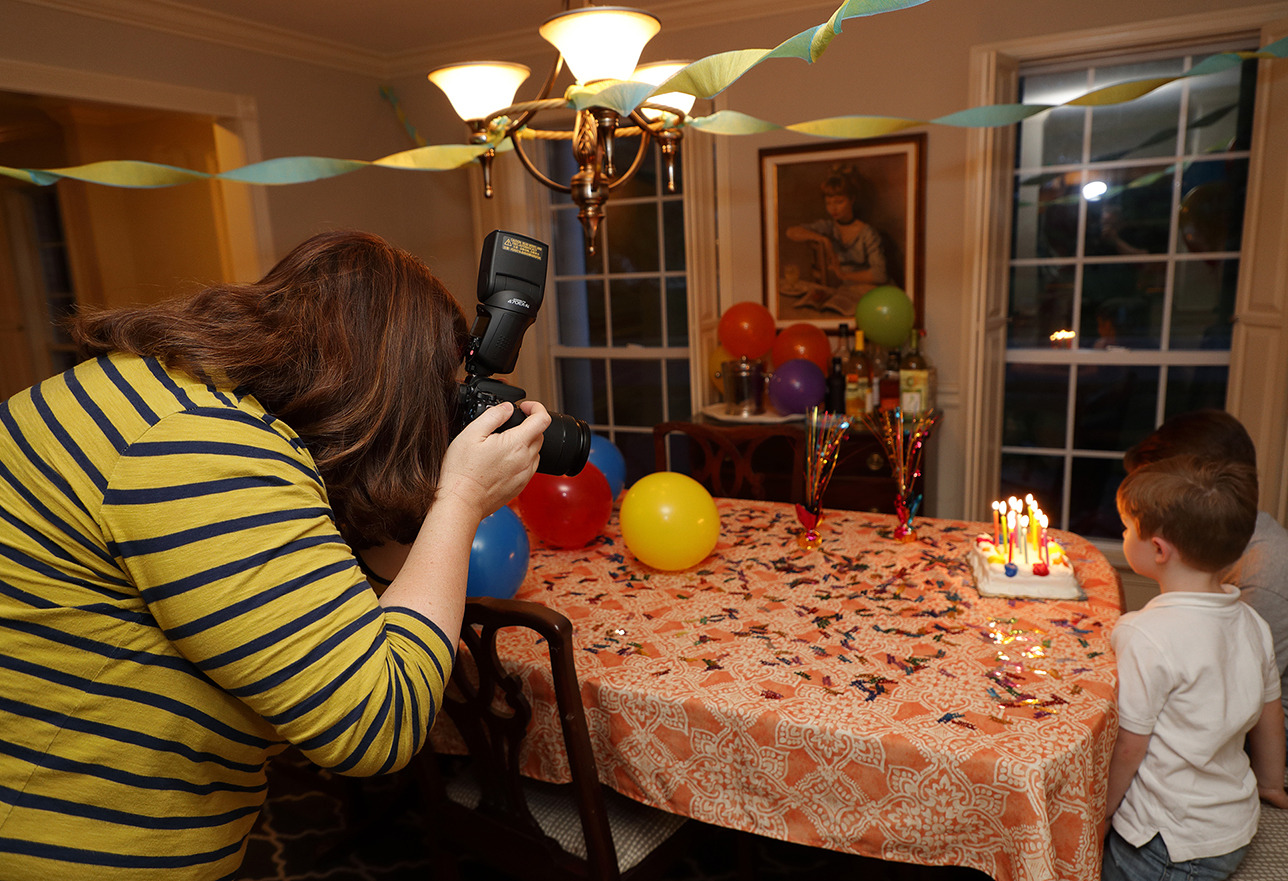 Mother taking photo of two young boys blowing out birthday candles