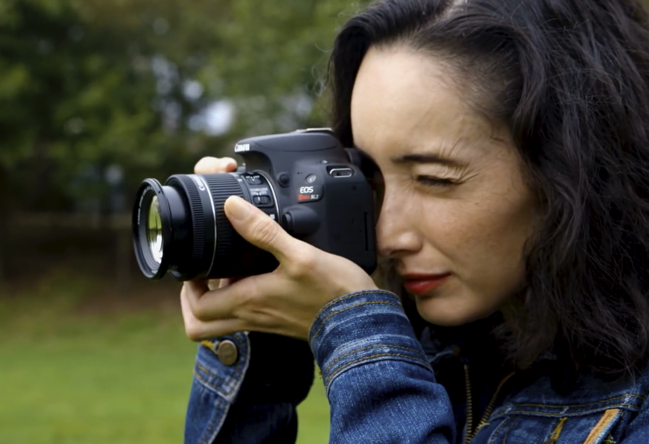 A woman looking through a camera